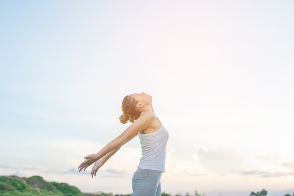concentrated-woman-stretching-her-arms-with-sky-background